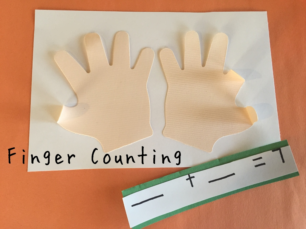 A mat with paper hands shows how to add and subtract by finger counting