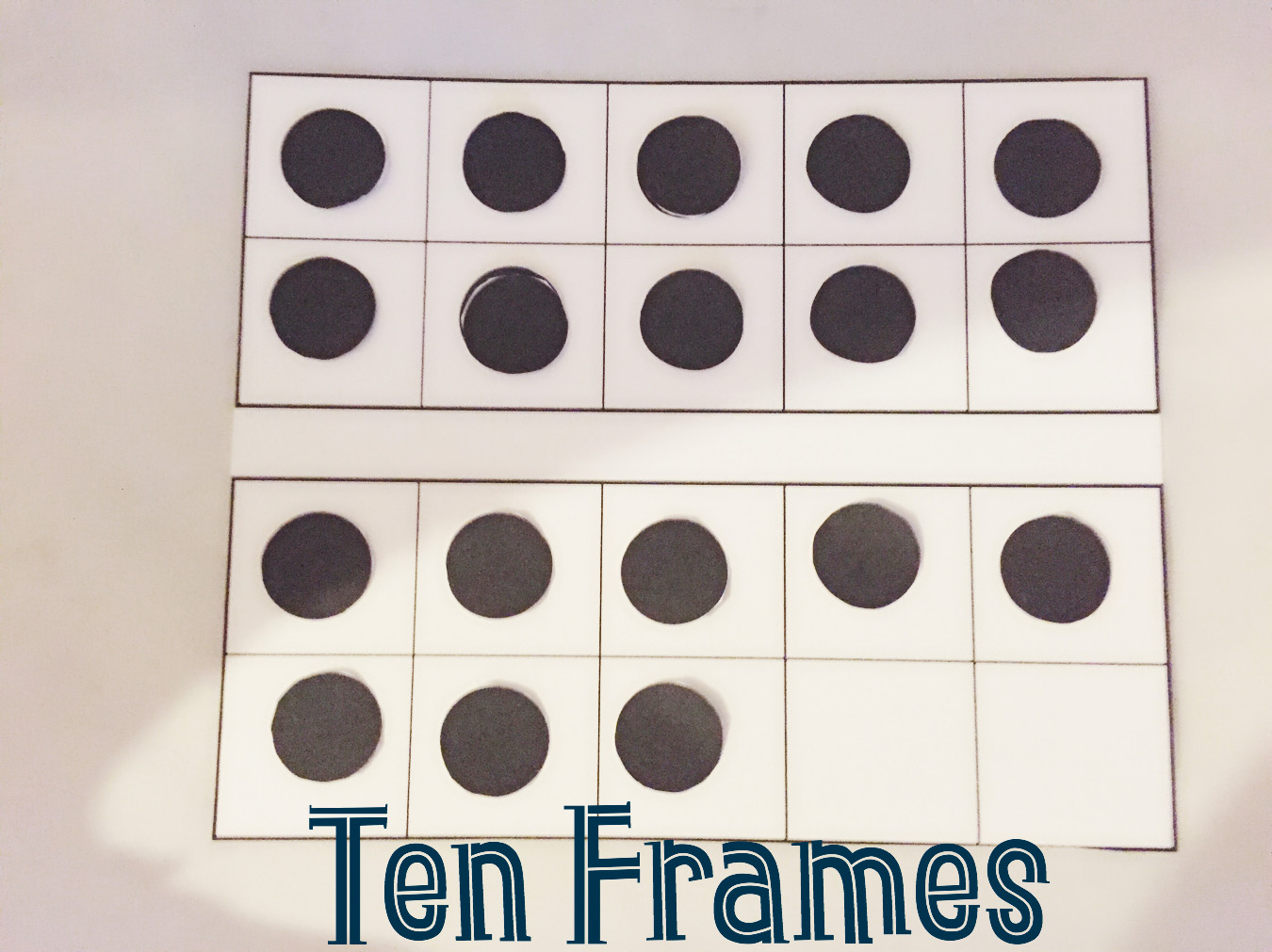 Ten frames with black paper dots help students add and subtract