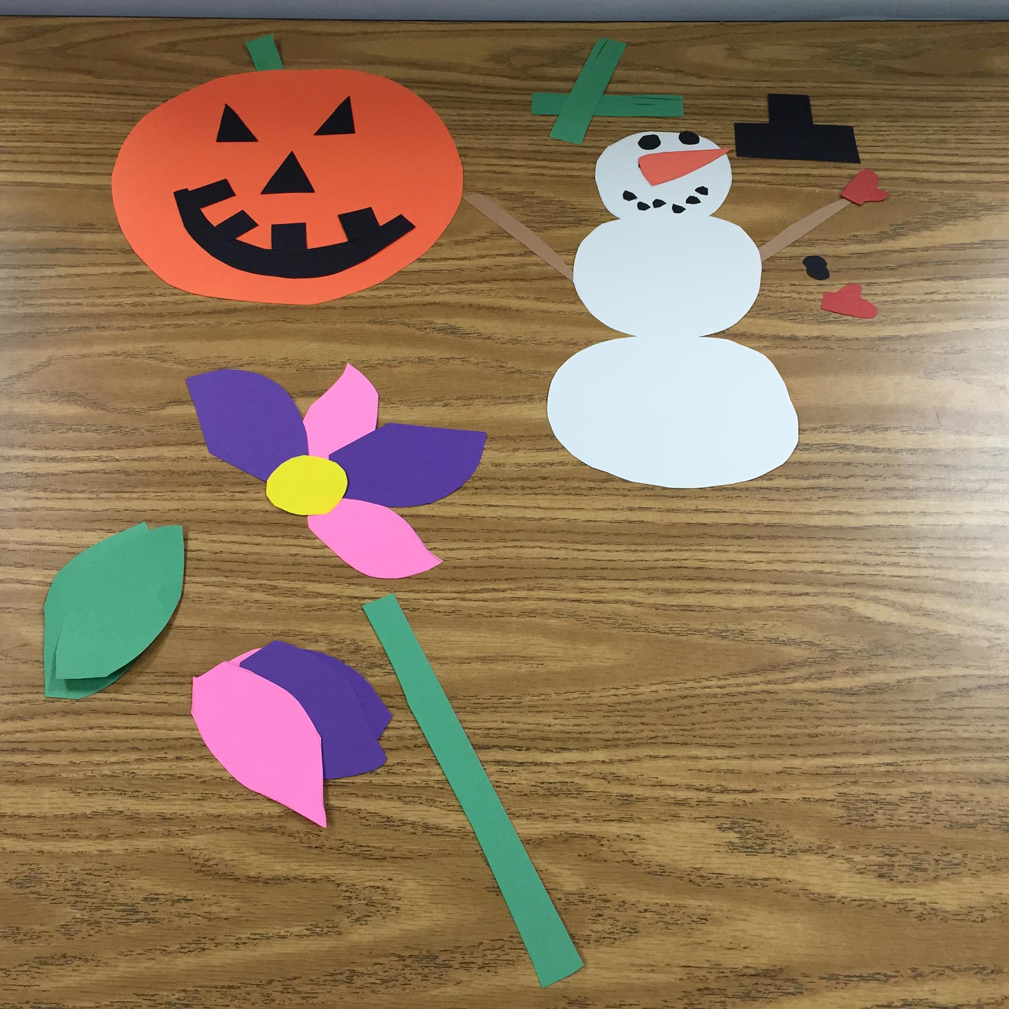 A jack-o-lantern, a snowman, and a flower with pieces