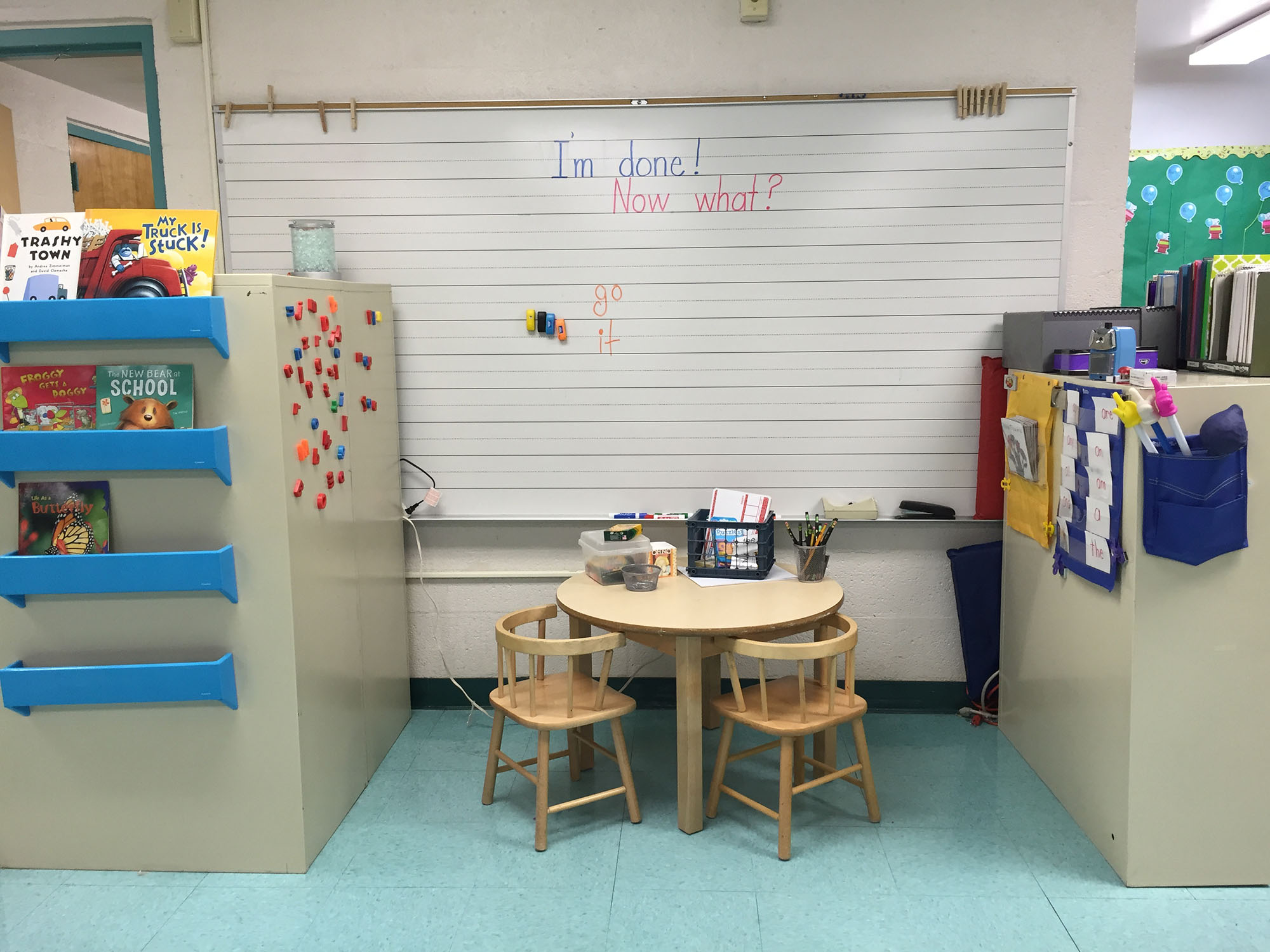 A center for unstructured learning, with books, supplies, a table, and a whiteboard