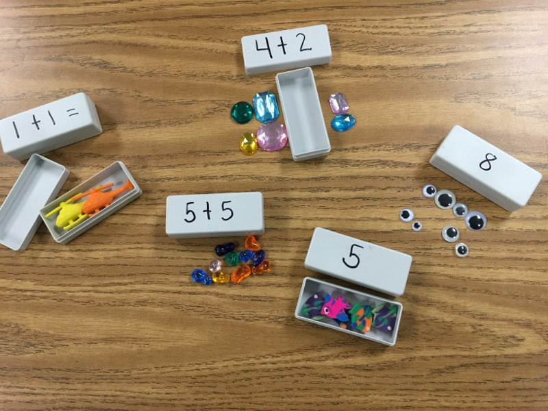 Math game with manipulatives inside boxes