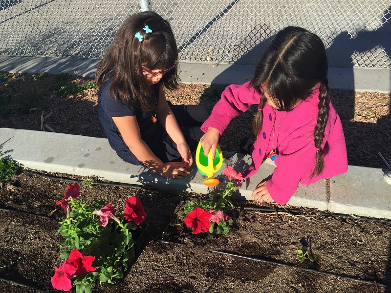 Two kids watering flowers for Earth Day