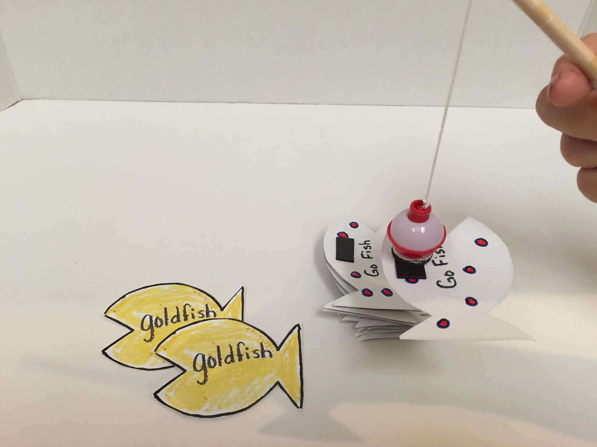 To play Go Fish, catch a card from the draw pile with the magnetic fishing pole