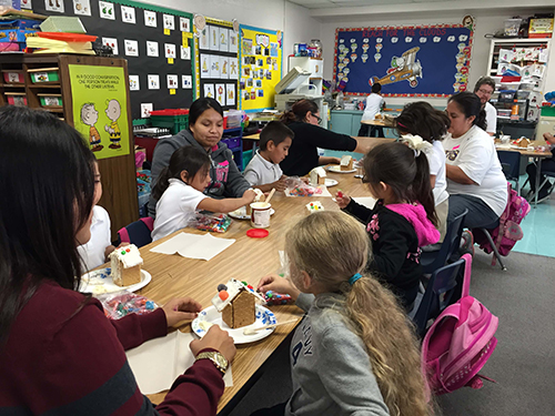 Parents and students making gingerbread houses