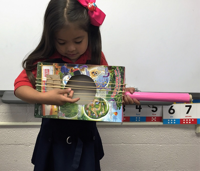 Kindergarteners Being Playful: A Girl Playing a Play Guitar