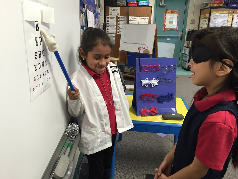 Kindergarteners Having Fun: Kids Practicing Letters With an Eye Chart