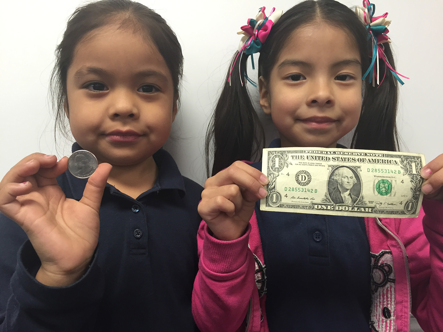 One child holding a quarter, and another holding a dollar bill