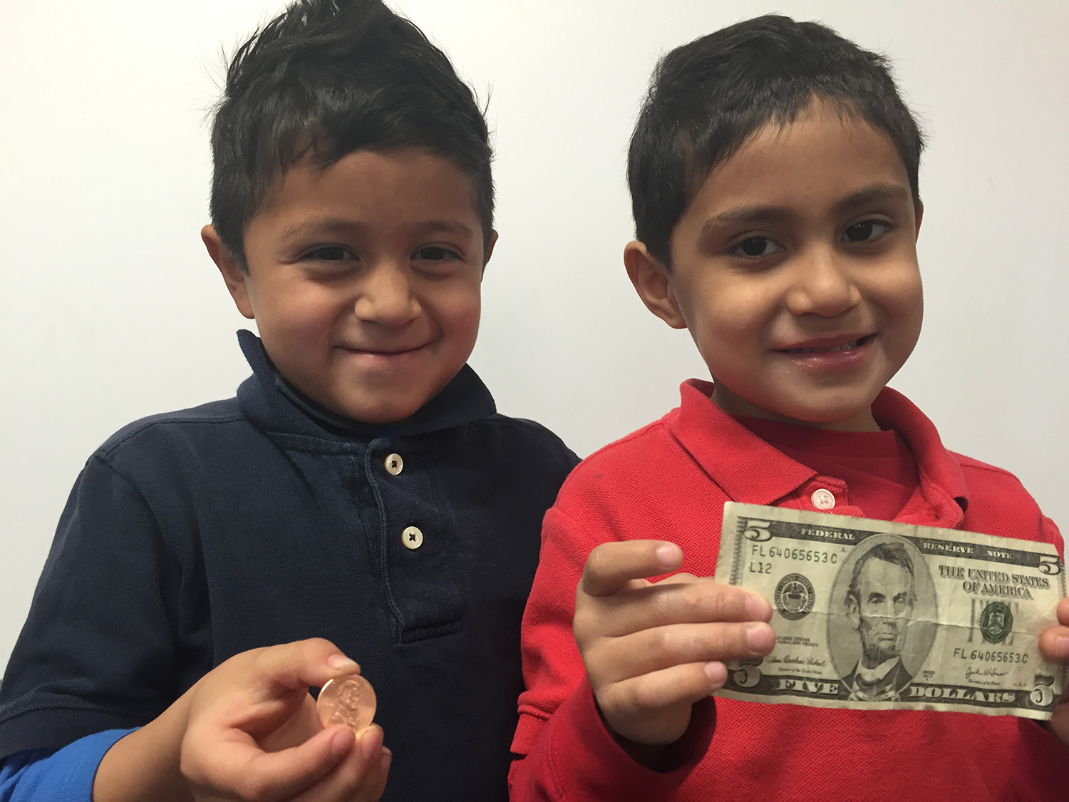 One child holding a penny, and another holding a five dollar bill