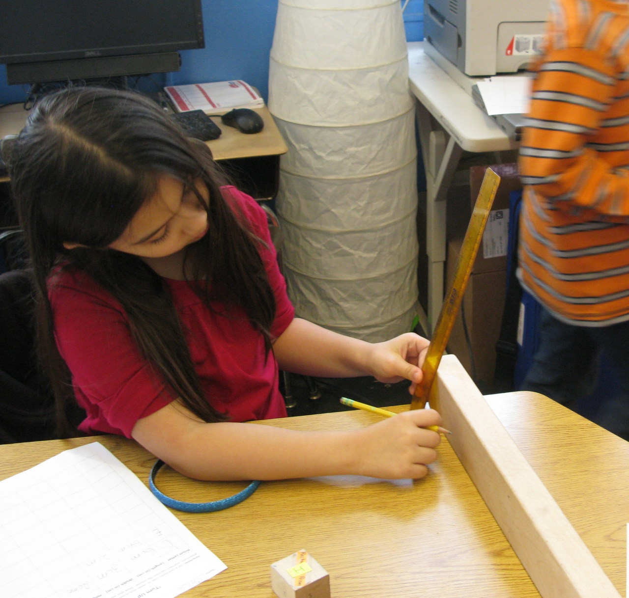 Finding the volume of wooden blocks through measurement.