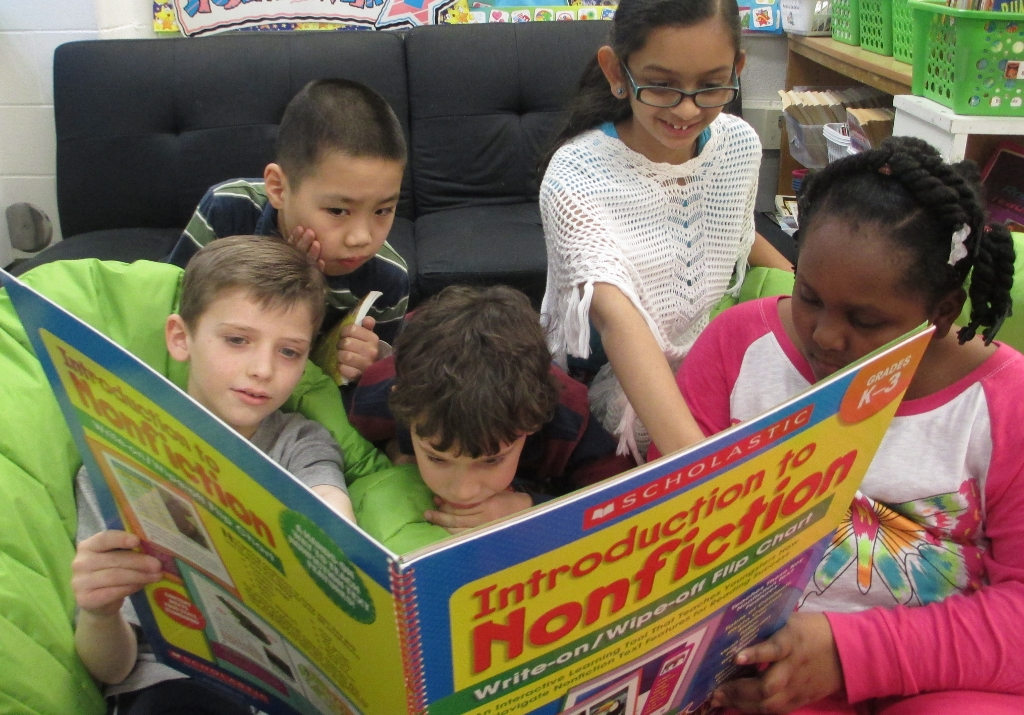 Kids looking at non-fiction book
