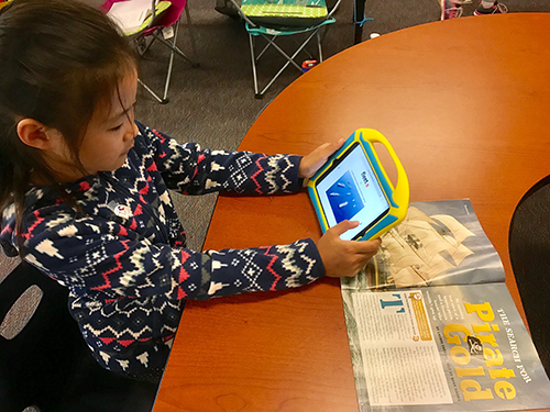 Girl watching vocabulary slideshow on iPad