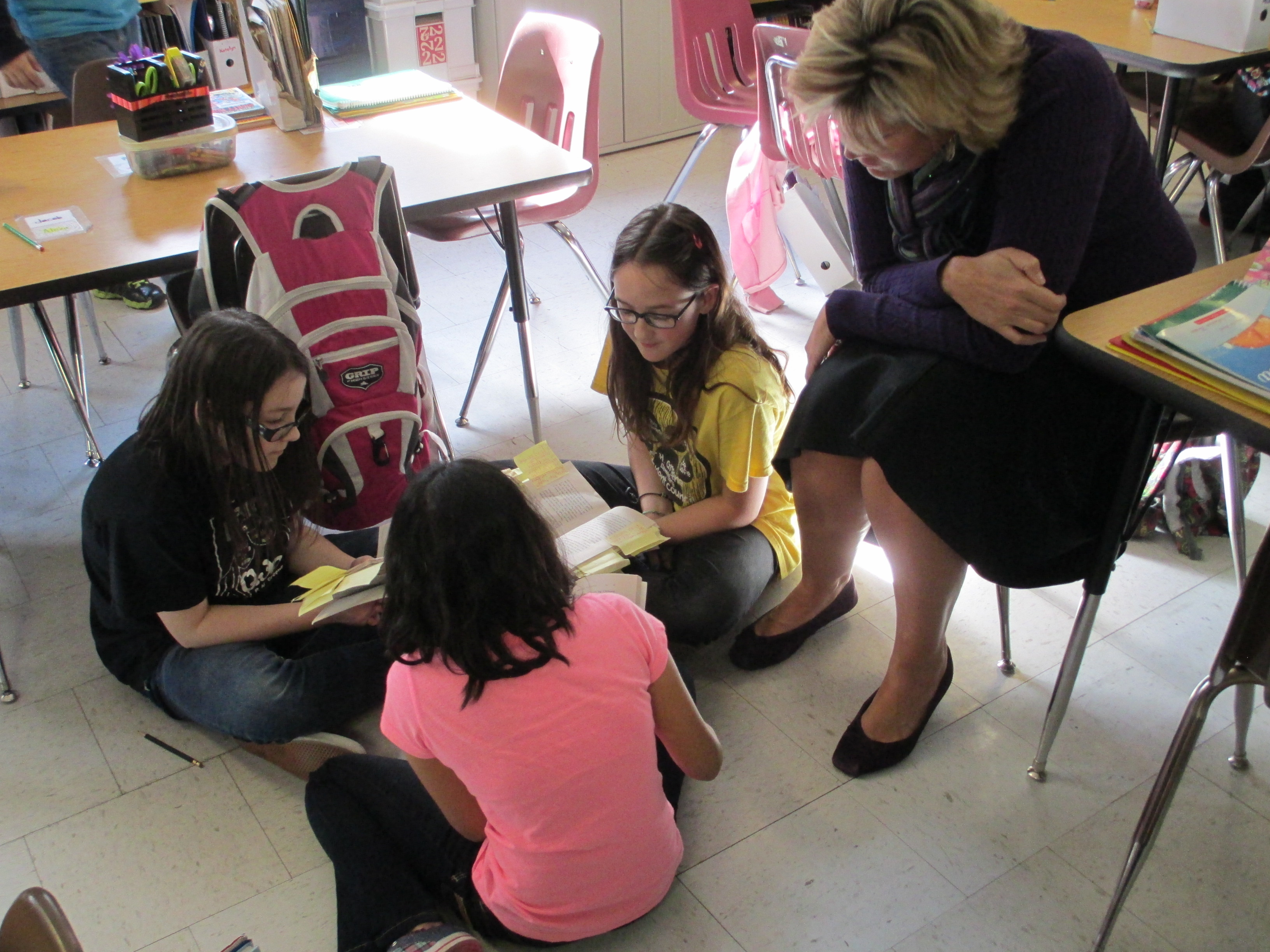 Students working in book club with teacher