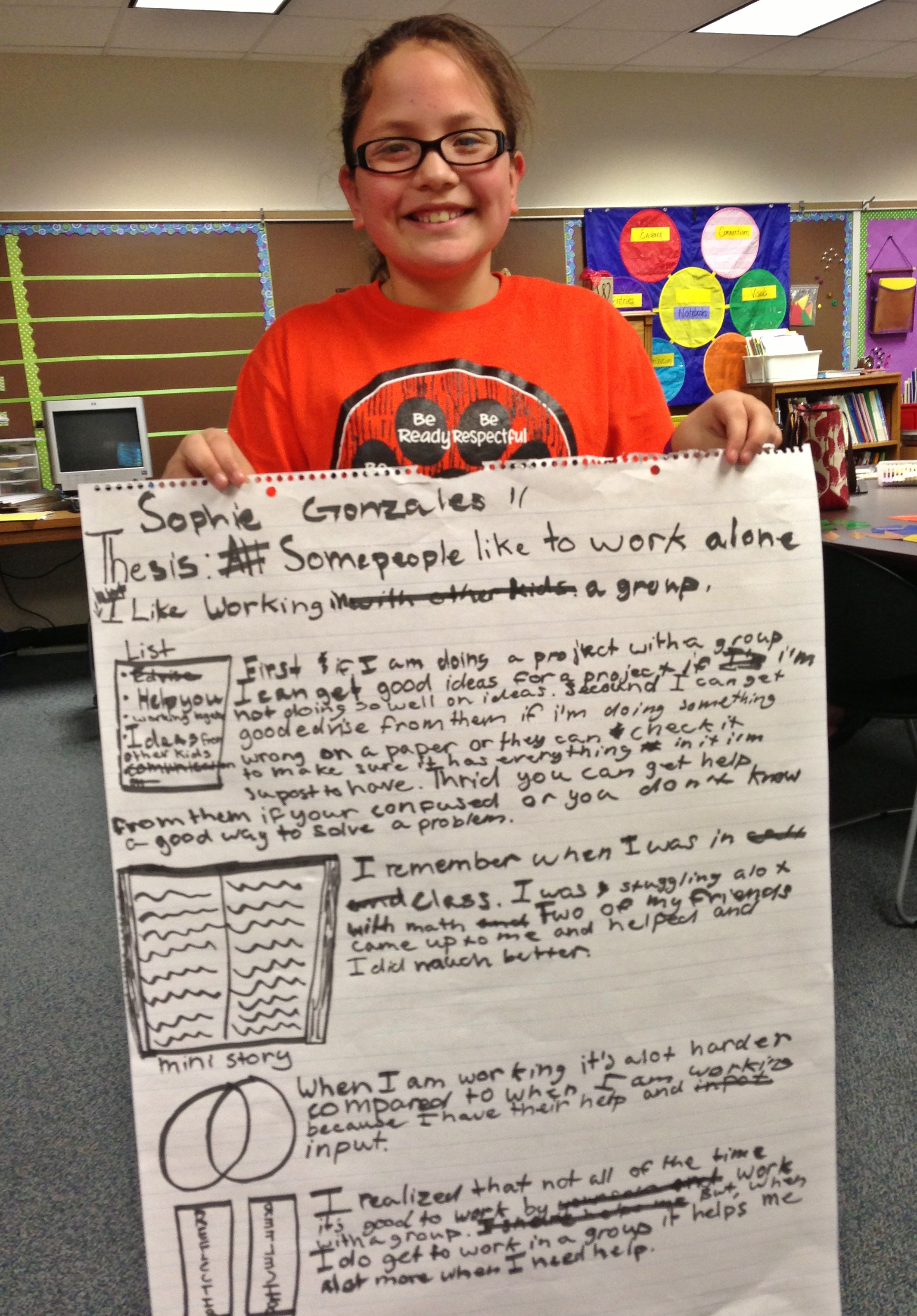 Student holding chart of writing plan