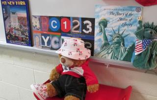 stuffed bear in New York garb sitting in front of books about New York