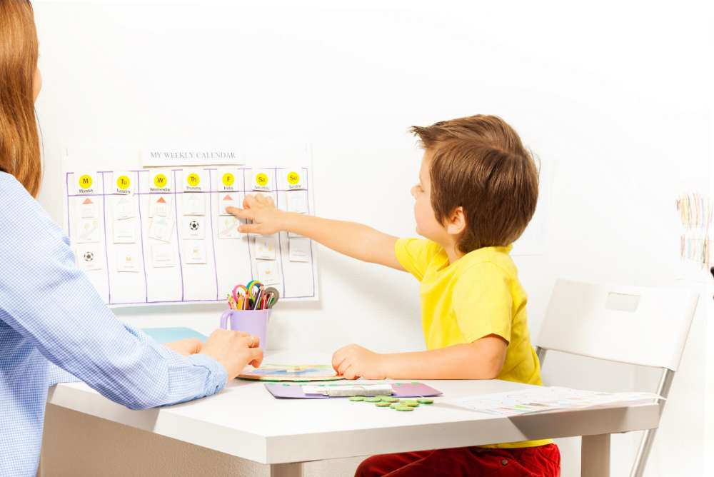 Boy points at activities on calendar learning days