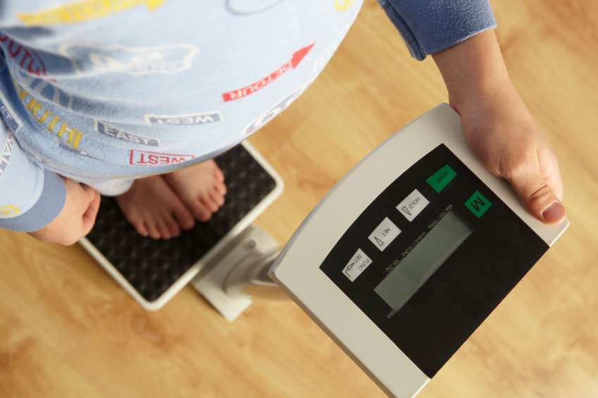 Young boy standing on digital scales cropped waist down